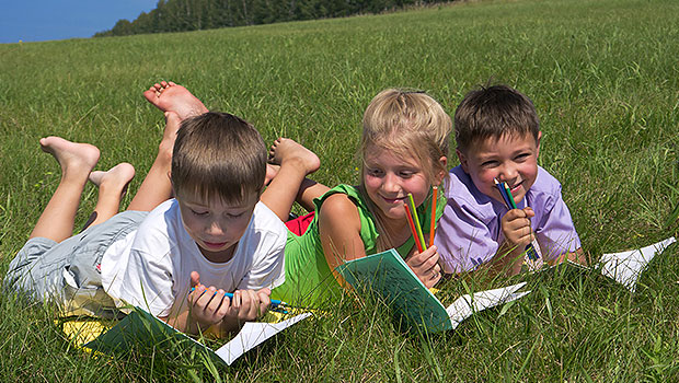 kids writing in the grass